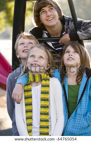 Group of children (10 to 15 years) standing together on playground on chilly day