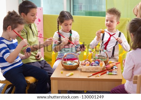 Group of children with aunt painting easter eggs - stock photo