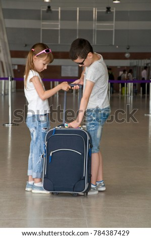 group of children with luggage in the airport. round the world trip on the plane. tourism