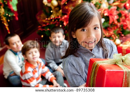 Group of children with presents next to the tree celebrating Christmas - stock photo