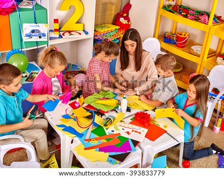 Group of children with teacher woman learn painting on paper at table  in  kindergarten . Art education. Top view. - stock photo