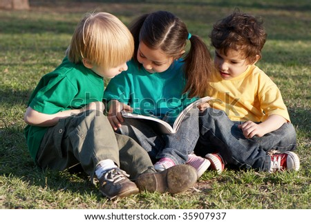 Group of children with the book on a grass in park - stock photo