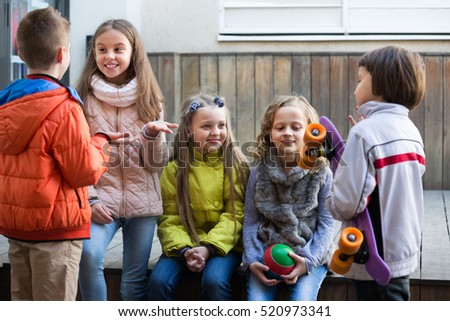 Group of children 7-8 years old with ball and skateboard chatting outdoors