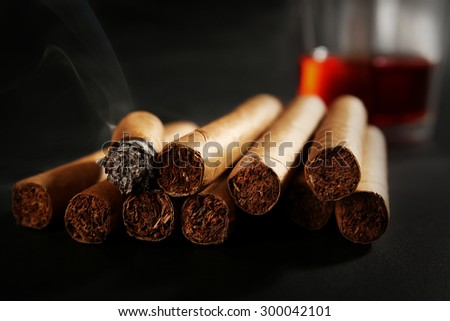 Group of cigars and burning one with whiskey on table, closeup - stock photo