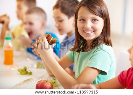 Group of classmates having lunch during break with focus on smiling girl with sandwich - stock photo