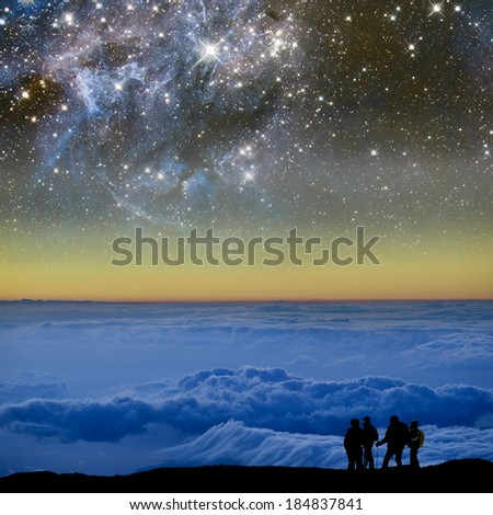 Group of climbers above the clouds, below the starry night sky. Elements of this image furnished by NASA.  - stock photo