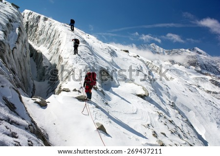 group of climbers on rope on glacier - sunny day on mountain - stock photo
