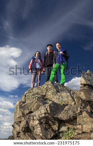 Group of climbers on the cliff. Three alpine climbers with gear stay on the rocky cliff. One male, two females, male is older, looks like father or even grandfather with daughters  - stock photo