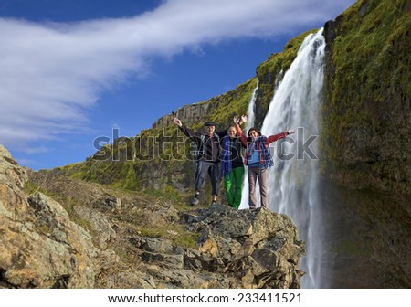 Group of climbers on the waterfall background. Three hikers of climbers - mature male and two young females - stays on the cliff against powerful waterfall. Horizontal composition - stock photo