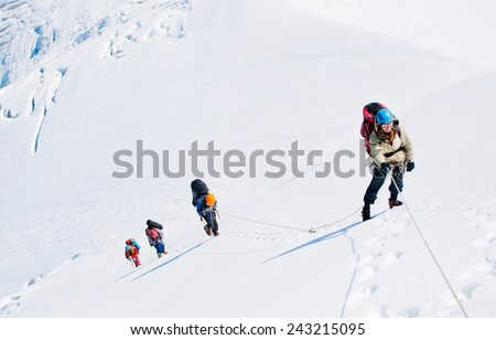 Group of  climbers reaching the summit - stock photo