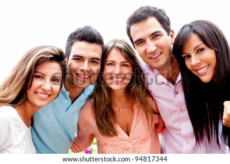 Group of close friends smiling outdoors and hugging - stock photo
