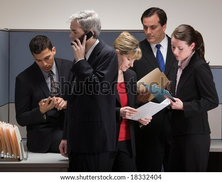 Group of co-workers in crisis meeting in cubicle - stock photo