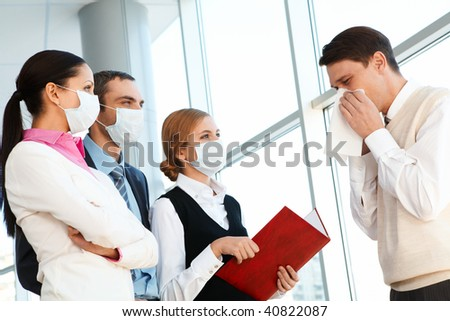 Group of co-workers in protective masks looking at sneezing man - stock photo