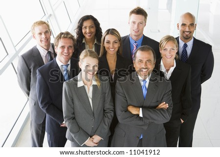 Group of co-workers standing in office space smiling ( - stock photo