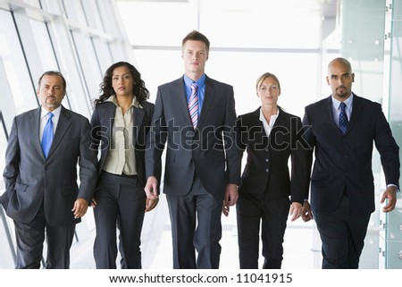Group of co-workers walking in office space - stock photo
