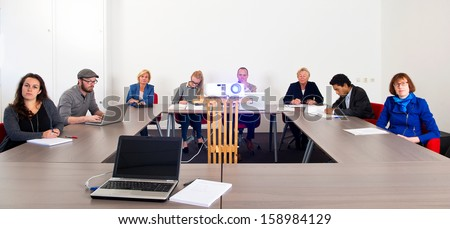 Group of colleagues attending a presentation in a meeting room - stock photo