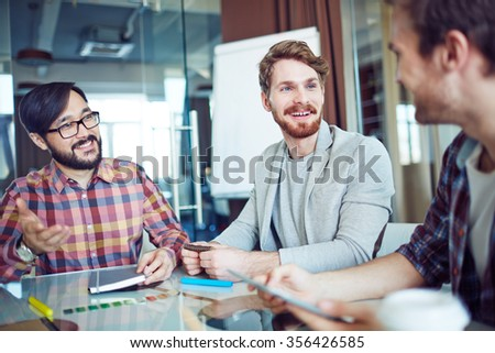 Group of colleagues consulting at meeting in office - stock photo