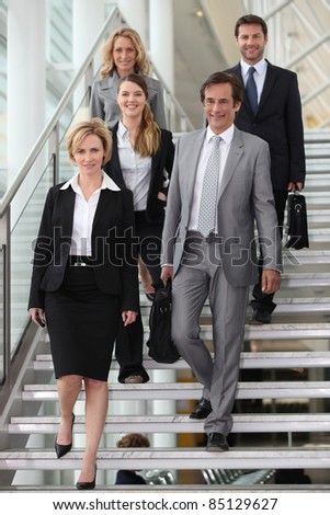 Group of colleagues descending stairs - stock photo