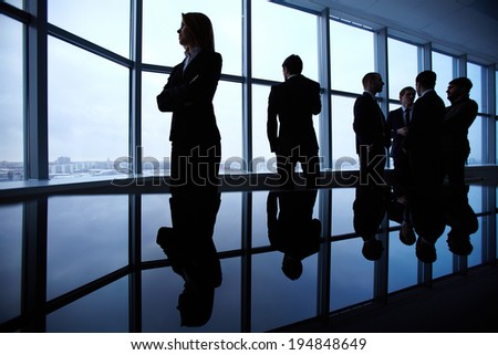 Group of colleagues standing against window in office