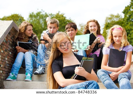 Group of college friends holding books - stock photo