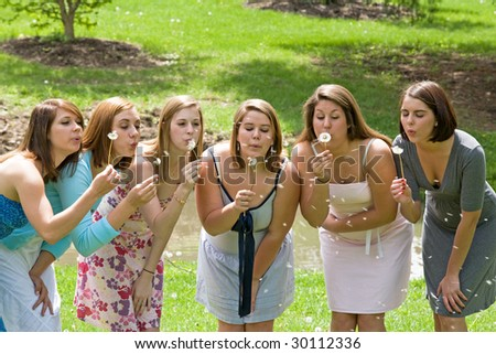 Group of College Girls Blowing Dandelion Seeds - stock photo
