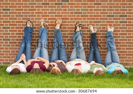 Group of College Girls With Legs on Wall - stock photo