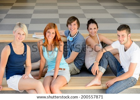 Group of college student friends sitting on bench looking camera - stock photo