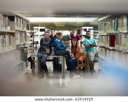 group of college students looking at camera in library. Horizontal shape, front view, full length, copy space