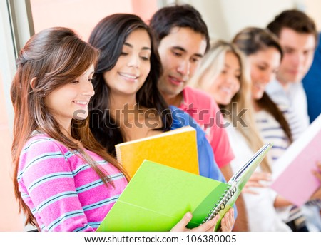 Group of college students looking at notebooks - stock photo