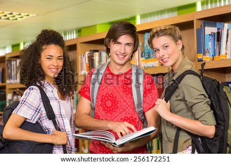 Group of college students reading book in the library