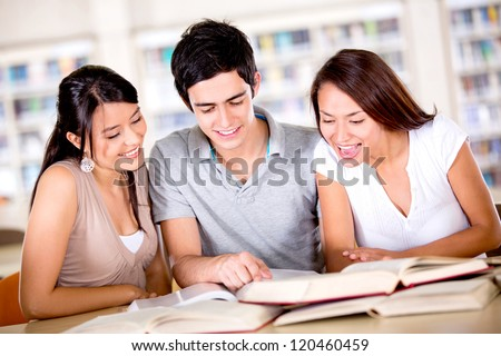 Group of college students studying at the library - stock photo