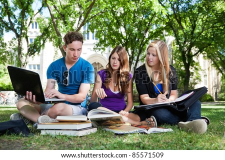 Group of college students studying together on campus ground - stock photo