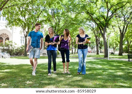 Group of college students walking in campus ground - stock photo