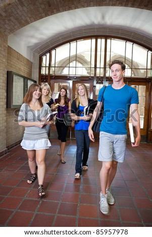 Group of college students walking through hall - stock photo