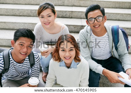 Group of college students with take-out coffee sitting on stairs