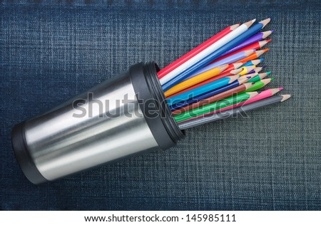Group of colored pencils in cup with metal. On the jeans texture. - stock photo