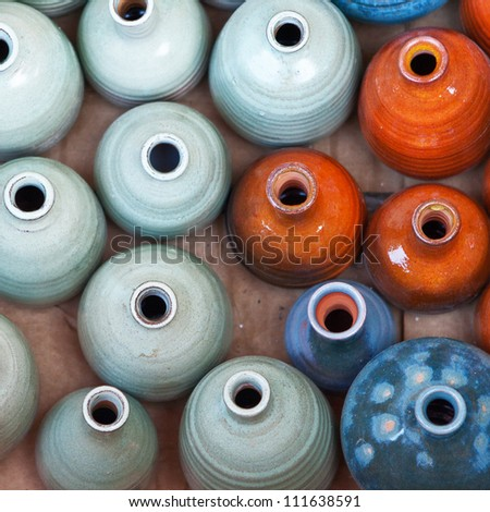 Group of colorful ceramic pots and vessels for sale. The simple form, mat surface, exquisite decoration,shining colors. Good for background.Israeli flea market.