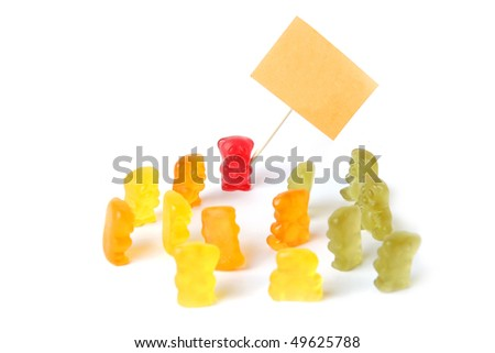 Group of colorful gummy bears holding an empty sign on white background - stock photo