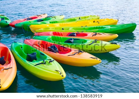 Group of colorful kayaks on water - stock photo