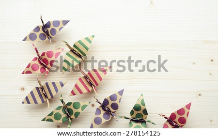 Group of colorful origami birds on wooden background - stock photo