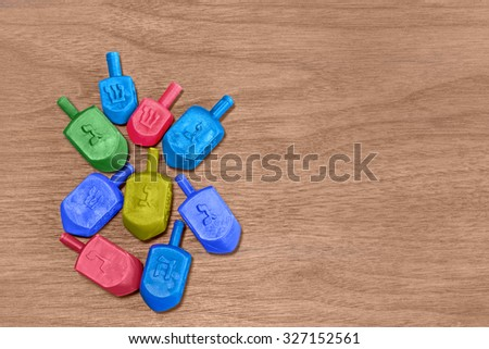 Group of colorful plastic Chanukah dreidels on worn wood grain texture background, top down view. Small dreidels with Hebrew letters nun, gimel, hey, shin. Drop shadow.  - stock photo