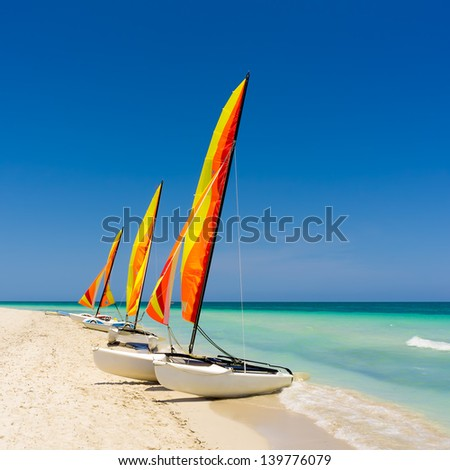 Group of colorful sailing boats on a calm and deserted beach in Cuba - stock photo