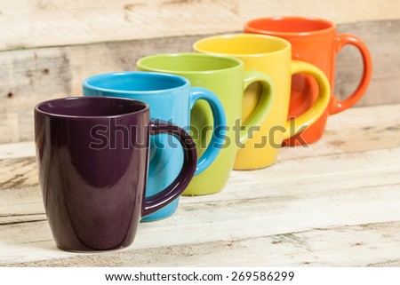Group of colorful tea cups on wooden background. - stock photo