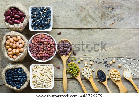 Group of colorful various beans or lentils and whole grains seeds or cereal in hemp sack and white cup. mung bean, peanut or groundnut, blackbean, red kidney bean, soybean, pinto beans. top view - stock photo