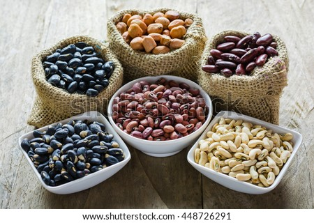 Group of colorful various beans or lentils and whole grains seeds or cereal in hemp sack and white cup. mung bean, peanut or groundnut, blackbean, red kidney bean, soybean, pinto beans - stock photo
