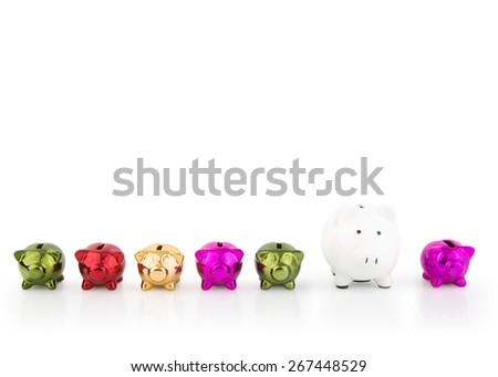 group of coloured Piggy Banks in a row with one white - stock photo