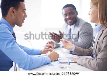 Group of confident business partners discussing data or explaining ideas at meeting - stock photo