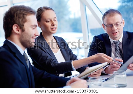 Group of confident business partners discussing paper at meeting - stock photo