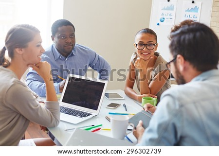Group of confident business partners discussing plans and data - stock photo