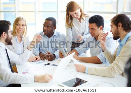 Group of confident business partners interacting at meeting - stock photo